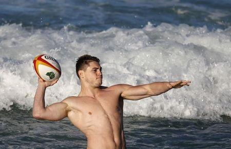 Australian Wallabies player O'Connor plays with a rugby ball during a recovery session at Coogee beach in Sydney