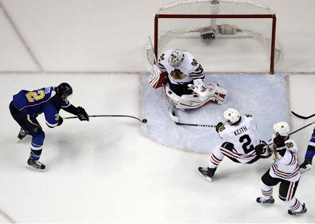 Chicago Blackhawks goalie Corey Crawford blocks a shot from St. Louis Blues' Chris Porter, left, as Blackhawks' Duncan Keith (2) and Jonathan Toews, right, watch during the first overtime in G