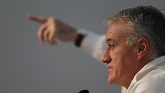 France's national soccer team coach Deschamps listens as media advisor points to a reporter during a news conference at the training camp in Clairefontaine