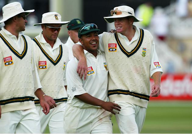 Paul Adams and Shaun Pollock of South Africa hug as they leave the field after they bowl England out