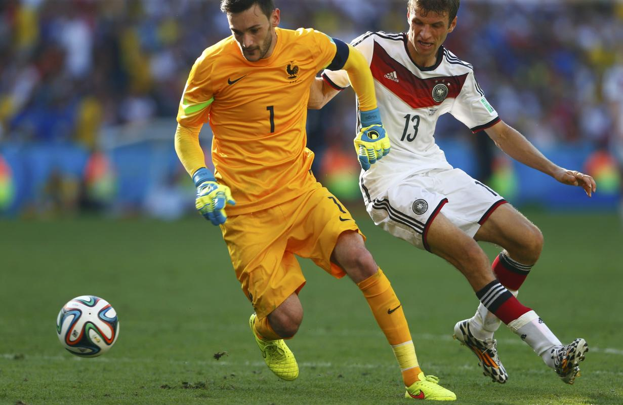 France's Lloris and Germany's Mueller run for the ball during their 2014 World Cup quarter-finals at the Maracana stadium in Rio de Janeiro