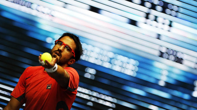 Serbia's Tipsarevic serves to France's Simon during their men's singles semi-final match at the Thailand Open 2012 tennis tournament in Bangkok