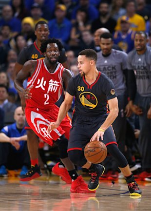 Patrick Beverley watches Stephen Curry closely. (Ezra Shaw/Getty Images)