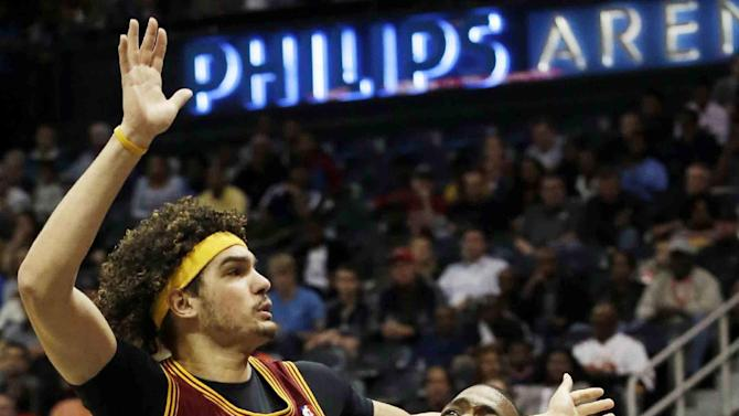 Atlanta Hawks forward Paul Millsap (4) is fouled as he tries to get past Cleveland Cavaliers center Anderson Varejao (17) in the first half of an NBA  basketball game Friday, Dec. 6, 2013, in Atlanta