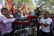 Activists from Shiv Sena, a Hindu hardline group, carry a motor bike as they shout slogans during a protest against the price hike in petrol, in Jammu