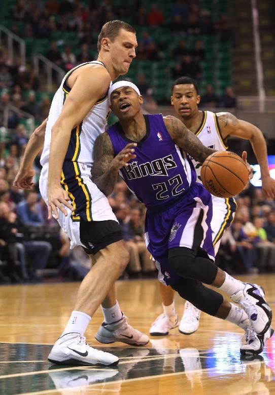 Utah Jazz's Andris Biedrins, left, defends as Sacramento Kings' Isaiah Thomas (22) drives the basket in the first half of an NBA basketball game on Saturday, Dec. 7, 2013, in Salt Lake City