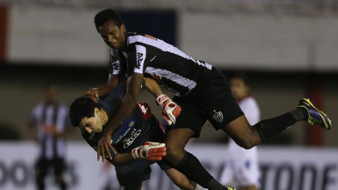 Jo of Brazil's Atletico Mineiro fights for the ball with goalkeeper Ignacio Don of Paraguay's Nacional during their Copa Libertadores soccer match in Ciudad del Este