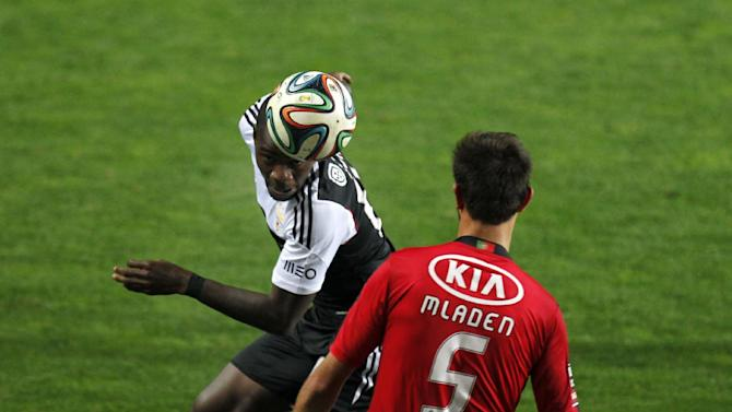 Benfica's Ola John, left, from The Netherlands, vies for a high ball with Olhanense's Sebastian Mladen, from Romania, during a Portuguese league soccer match between Benfica and Olhanense at the Algarve stadium in Faro, southern Portugal, Sunday, Dec. 15, 2013. Benfica won 3-2