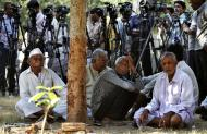 Unidentified relatives of accused and TV cameramen wait outside the district court in Mehsana, about 40 kilometers (25 miles) north of Ahmadabad, India, Wednesday, Nov. 9, 2011. The court convicted 31 Hindus for killing dozens of Muslims by setting a building on fire in Gujurat state during one of India's worst rounds of communal violence nine years ago. (AP Photo/Ajit Solanki)