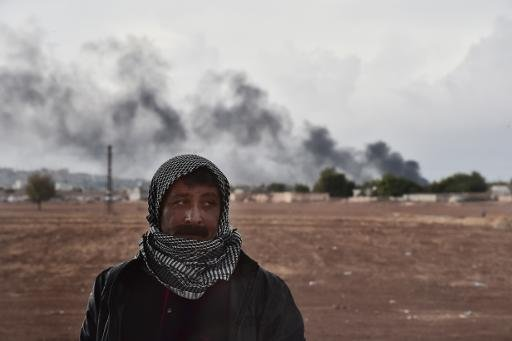 A Kurdish man stands close to the Turkish-Syrian border as smoke rises from the Syrian town of Kobane, as seen from the southeastern village of Mursitpinar, in the Sanliurfa province, on October 16, 2014