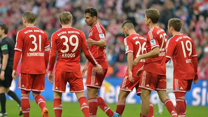 Bayern's players walk over the pitch after scoring during the German first division Bundesliga soccer match between FC Bayern Munich and SC Freiburg in Munich, Germany, on Saturday, Feb. 15, 2014