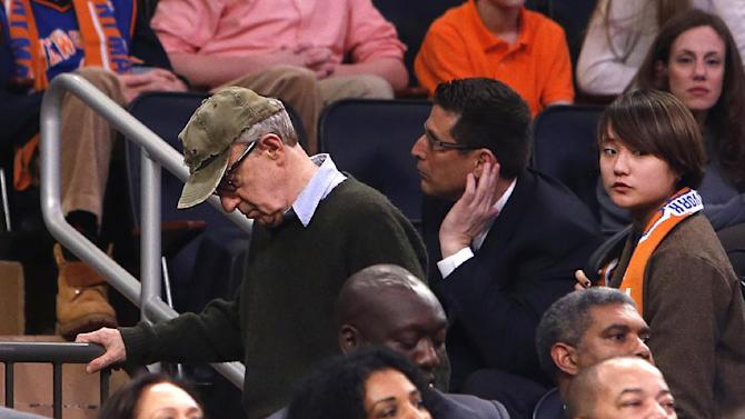 Filmmaker Woody Allen, left, leaves late in the fourth quarter of an NBA basketball game between the Miami Heat and the New York Knicks Saturday, Feb. 1, 2014, in New York.  Miami won 106-91