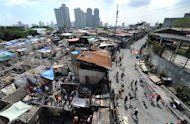 Squatters throw rocks at a demolition crew during a demolition in Manila's financial district on April 28, 2011. The Philippine government plans to move about 100,000 squatters from their homes on crucial waterways in Manila by June as a flood control measure and for their own safety