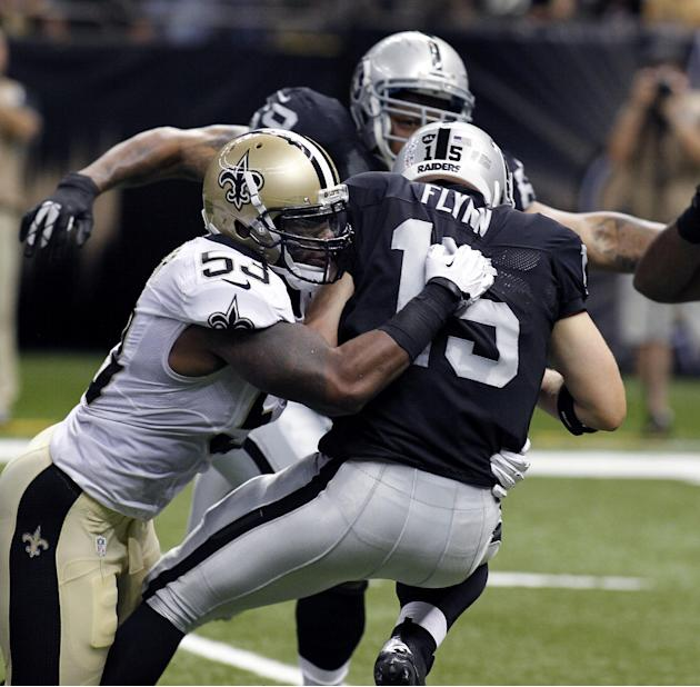 In this Aug. 16, 2013 file photo, Oakland Raiders quarterback Matt Flynn (15) is sacked by New Orleans Saints linebacker Ramon Humber (53) in the first half of an NFL preseason football game at the Me
