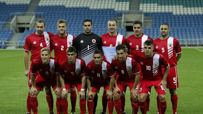 Gibraltar's players Danny Higginbotham, Scott Wiseman, goalkeeper Jordan Perez, Roy Chipolina, Joseph Chipolina, Ryan Casciaro, upper row from left, and Adam Priestley, Jeremy Lopez, Robert Guilling, Daniel Duarte and Liam Walker, lower row from left, pose for the media before a friendly soccer match between Gibraltar and Slovakia at the Algarve stadium in Faro, southern Portugal, Tuesday, Nov. 19, 2013. Gibraltar played its first international soccer match as a new full member of the UEFA after they were accepted in May. The match ended in a 0-0 draw