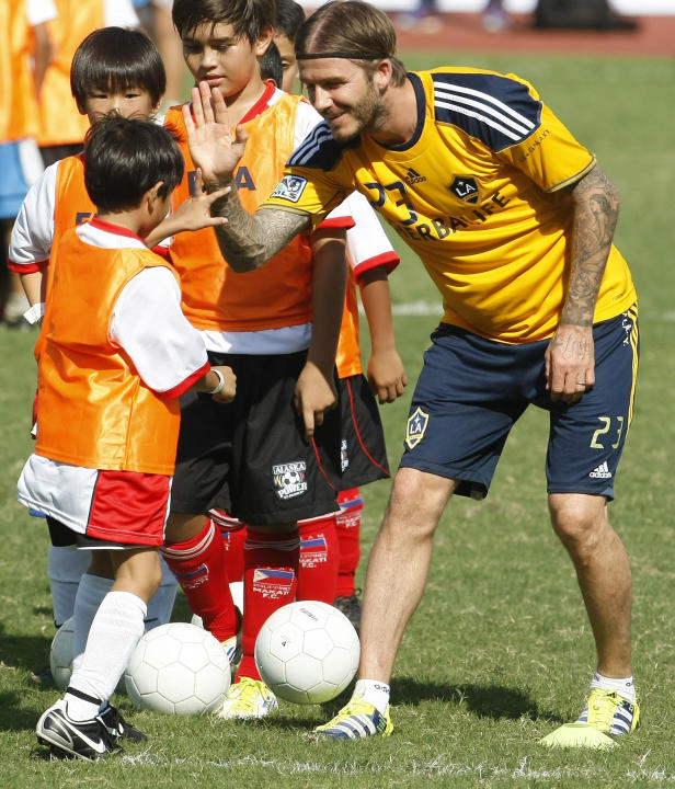 British soccer player David Beckham of the Los Angeles Galaxy exchanges high-fives to Filipino children while conducting football clinic at the Rizal Memorial Football Stadium Friday Dec. 2, 2011 in M