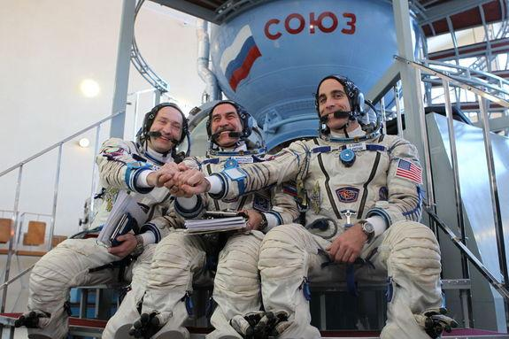 At the Gagarin Cosmonaut Training Center in Star City, Russia, Expedition 35/36 Flight Engineer Chris Cassidy (right), Soyuz Commander Pavel Vinogradov (center) and Flight Engineer Alexander Misurkin clasp hands for photographers prior to the s