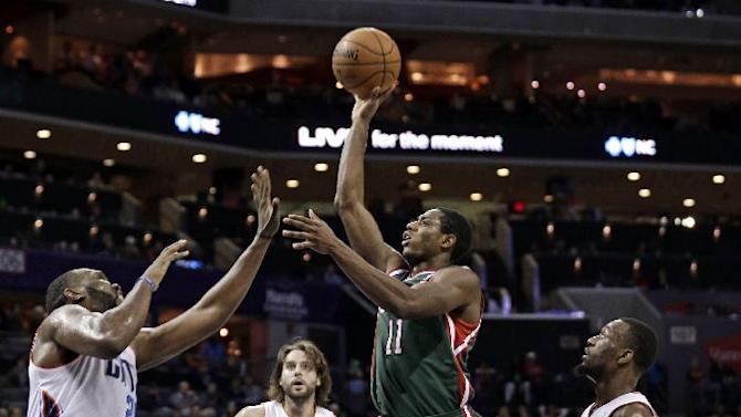Milwaukee Bucks' Brandon Knight, second from right, shoots between Charlotte Bobcats' Al Jefferson, left, Kemba Walker, right, and Josh McRoberts, back, during the second half of an NBA basketball game in Charlotte, N.C., Monday, Dec. 23, 2013. The Bobcats won 111-110 in overtime