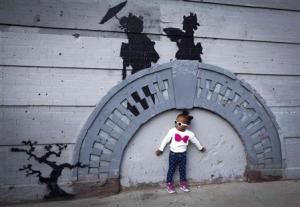 A child poses for a photo under a new art piece by British graffiti artist Banksy in the Brooklyn borough of New York