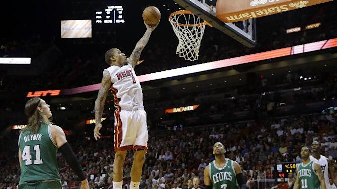 Miami Heat's Michael Beasley (8) shoots as Boston Celtics' Kelly Olynyk (41), Jared Sullinger (7) and Courtney Lee (11) stand by during the first half of an NBA basketball game Saturday, Nov. 9, 2013, in Miami