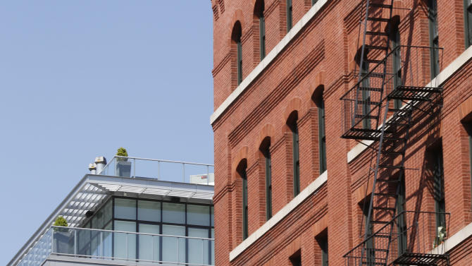 A modern luxury glass apartment building, left, sits across the street from an older red brick apartment, the home of photograher Arne Svenson, Thursday, May 16, 2013 in New York. Residents of a New York luxury apartment building are livid over an exhibition of photos secretly snapped through their apartment windows. (AP Photo/Bebeto Matthews)