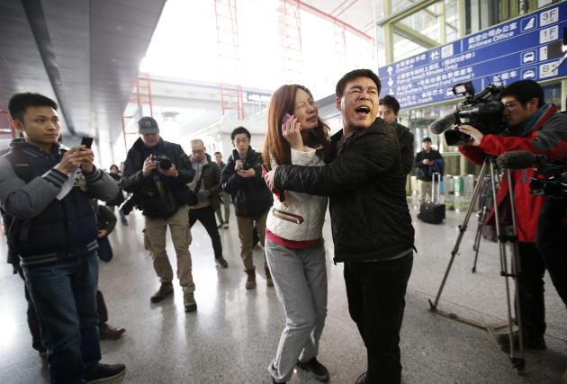 A relative (woman in white) of a passenger onboard Malaysia Airlines flight MH370 cries as she talks on her mobile phone at the Beijing Capital International Airport in Beijing March 8, 2014. The Malaysia Airlines flight carrying 227 passengers and 12 crew lost contact with air traffic controllers early on Saturday en route from Kuala Lumpur to Beijing, the airline said in a statement. Flight MH 370, operating a Boeing B777-200 aircraft departed Kuala Lumpur at 12.21 a.m. (1621 GMT Friday) and had been expected to land in the Chinese capital at 6.30 a.m. (2230 GMT) the same day. REUTERS/Kim Kyung-Hoon (CHINA - Tags: TRANSPORT DISASTER TPX IMAGES OF THE DAY)