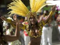 """In this photo taken Saturday, Feb. 2, 2013, """"passista,"""" or samba dancer Diana Prado performs in a carnival parade at central station in Rio de Janeiro, Brazil. A call center supervisor by day the 27-year-old's double life is split down the middle, between the glitz and glam, feathers and body paint of Carnival and the workaday office reality of head-sets and cubicles. (AP Photo/Felipe Dana)"""