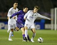 Defender Jovlon Ibrokhimov (R) of Uzbekistan's Bunyodkor is tackled by Yojiro Takahagi of Japan's Sanfrecce Hiroshima during the AFC champions league group G match in Hiroshima, western Japan on February 27, 2013. Bunyodkor won the game 2-0