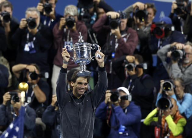 Nadal of Spain raises his trophy after defeating Djokovic of Serbia in their men's final match at the U.S. Open tennis championships in New York