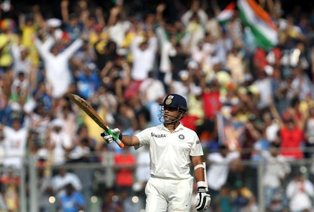 Indian cricketer Sachin Tendulkar lifts his bat after scoring half century during the 2nd day of the 2nd Test Match between India and West Indies at Wankhede Stadium in Mumbai on Nov.14, 2013. (Photo: