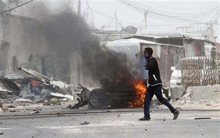 A man talks on his mobile phone as he walks at the scene of an explosion near the entrance of the airport in Somalia's capital Mogadishu February 13, 2014. REUTERS/Feisal Omar