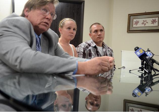 Francis Pusok, right, and his fiancee Joline Bindner, listen as his attorney Jim Terrell speaks during a press conference, Tuesday, Sept. 1, 2015, in Victorville, Calif. San Bernardino County District