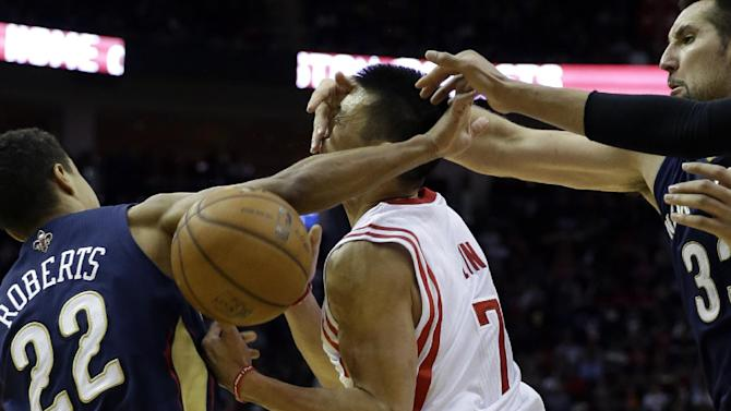 Houston Rockets' Jeremy Lin (7) is hit in the face as he is fouled by New Orleans Pelicans' Ryan Anderson (33) as Brian Roberts (22) also defends during the third quarter of an NBA basketball game on Saturday, Dec. 28, 2013, in Houston. The Rockets won 107-98