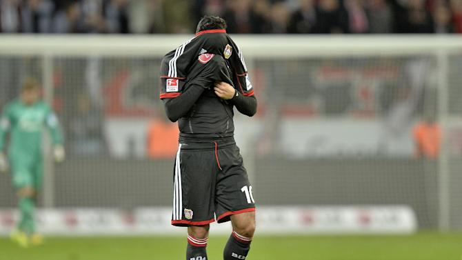 Leverkusen's Emre Can hides under his shirt after his team lost the German Bundesliga soccer match between Bayer Leverkusen and FC Schalke 04 in Leverkusen,  Germany, Saturday, Feb. 15, 2014. Leverkusen was defeated by Schalke 2-1