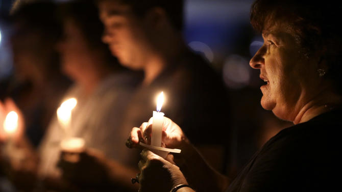 Denise Recatto, right, of Baton Rouge, La., joins in a song with other Elvis Presley fans as they take part in a candlelight vigil at Graceland, Presley's Memphis, Tenn. home, on Wednesday, Aug. 15, 2012. Fans from around the world are at Graceland to commemorate the 35th anniversary of Presley's death. (AP Photo/Mark Humphrey)