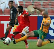 Oman's Saad Suhail (C) fights for the ball with Australia's Sasa Ognenovski (R) during their group B 2014 World Cup Asian qualifying football match in Muscat. The match ended in a 0-0 draw