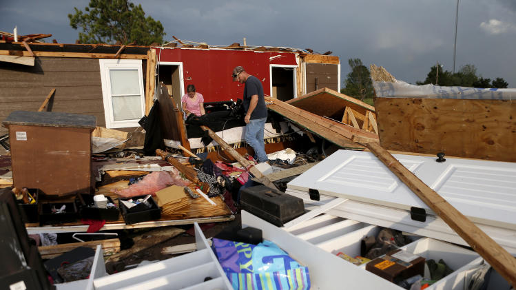Nancy and Jason Townsend sort through belongings after their home was hit by a tornado in Carney, Okla., Sunday, May 19, 2013. The Townsends left their home to avoid the tornado. (AP Photo/The Oklahoman, Bryan Terry)