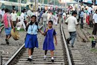 Indian school girls walk on the tracks as passengers wait near the platform of Sealdah train station for the resumption of services during a power failure in Kolkata