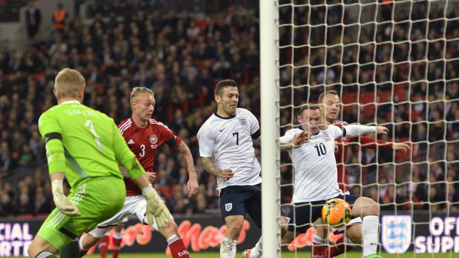 England's Rooney lunges for the ball in front of Denmark's goal post during their international friendly soccer match at Wembley stadium in London