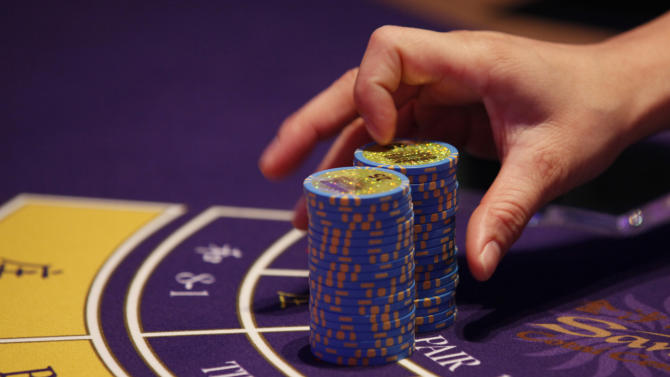 FILE - In this Sept. 20, 2012 file photo, a croupier counts the chips at a baccarat gaming table inside a casino during the opening day of Sheraton Macao Hotel at the Sands Cotai Central in Macau. Casino revenue in Macau climbed 13.5 percent last year to a record $38 billion, as the Asian gambling hub reinforced its position as the world's biggest gambling market, according to data posted on the Gaming Inspection and Coordination Bureau on Wednesday, Jan. 2, 2013. (AP Photo/Kin Cheung, File)