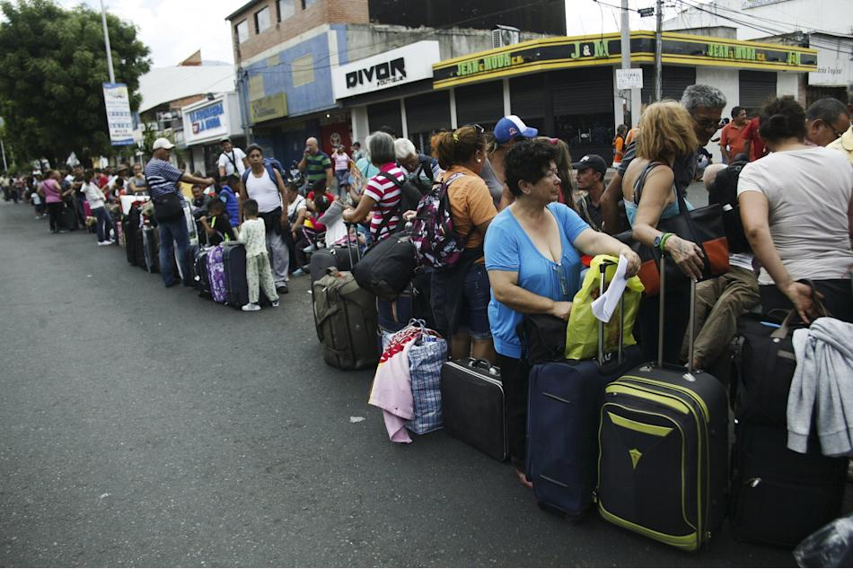 People queue while they wait to cross the border to Colombia at San Antonio in Tachira state