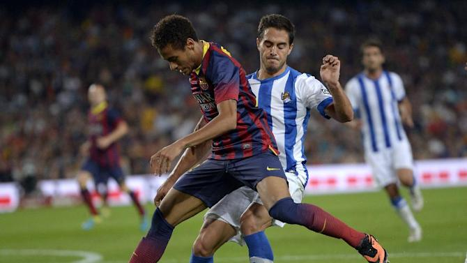FC Barcelona's Neymar, from Brazil, left, duels for the ball against Real Sociedad's Javi Ros during a Spanish La Liga soccer match at the Camp Nou stadium in Barcelona, Spain, Tuesday, Sept. 24, 2013