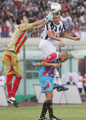 Juventus' Giorigo Chiellini, top right, and Catania goalie Mariano Gonzalo Andujar, of Argentina, jump for the ball during a Serie A soccer match between Juventus and Catania, at Catania's Angelo Massimino Stadium, Italy, Sunday, Sept. 25, 2011. (AP Photo/Jonathan Moscrop, LaPresse) ITALY OUT