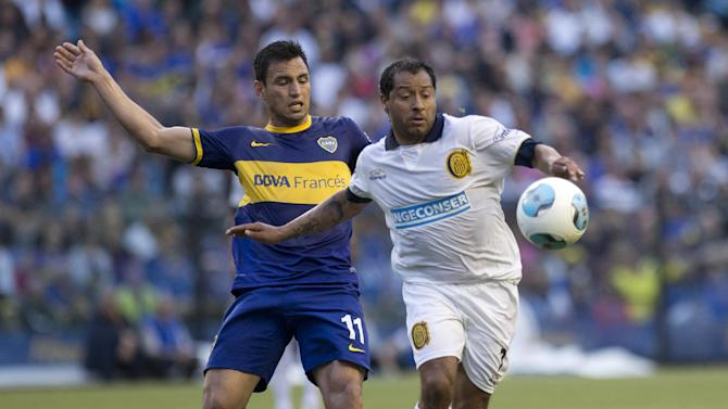 Boca Juniors' Juan Sanchez Mino, left, vies for the ball with Rosario Central's Hernan Encina during an Argentina's league soccer match in Buenos Aires, Argentina, Sunday, Oct. 13, 2013