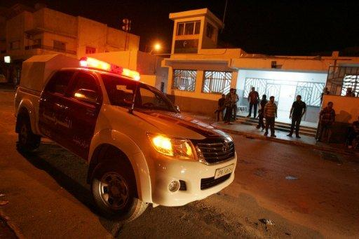 Libyan police officers stand on high alert after a car exploded near a police station in Libya's eastern city of Benghazi. A police officer told AFP that two of his colleagues were injured in subsequent clashes