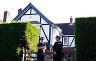 British police officers stand outside a house believed to be the British home of a family shot dead in their car in the French Alps. Investigators into the murders were pinning their hopes Friday on the seven-year-old girl wounded in the attack, as their probe appeared to make little headway