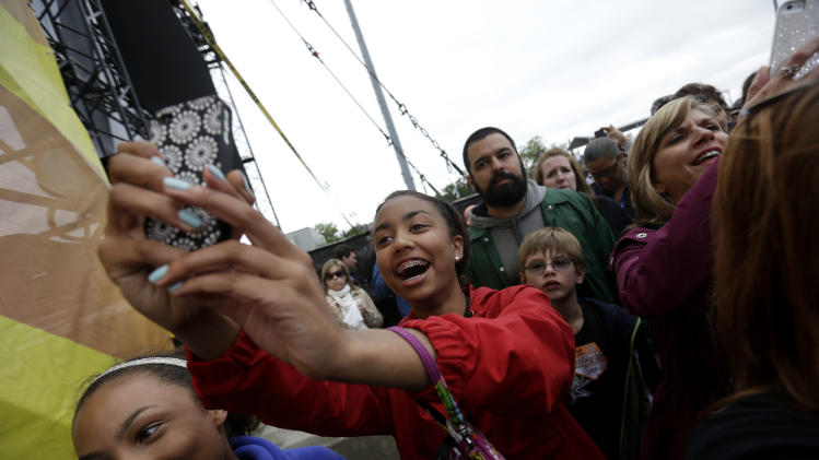 Fans take photos of the band Maroon 5 at the New Orleans Jazz and Heritage Festival in New Orleans, Friday, May 3, 2013. (AP Photo/Gerald Herbert)