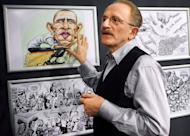 "Kallaugher points to drawing of US President Barack Obama during an exhibition at the National Museum of Contemporary Art in Bucharest. Political cartoons are ""on the frontline of freedom"" as recent attacks on cartoonists in Iran and Syria showed, famous American cartoonist Kevin KAL Kallaugher told AFP in Bucharest"