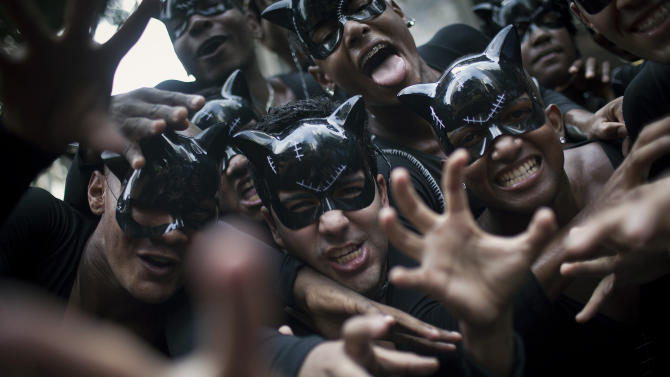 "Revelers dressed as cat-woman joke as they pose for photos during the ""Cordao da Bola Preta"" street carnival parade in Rio de Janeiro, Brazil, Saturday, Feb. 9, 2013. According to Rio's tourism office, Rio's street Carnival this year will consist of 492 block parties, attended by an estimated five million Carnival enthusiasts. (AP Photo/Felipe Dana)"