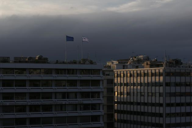 A Greek national flag and a European Union flag flutter atop the Finance Ministry building during sunset in Athens